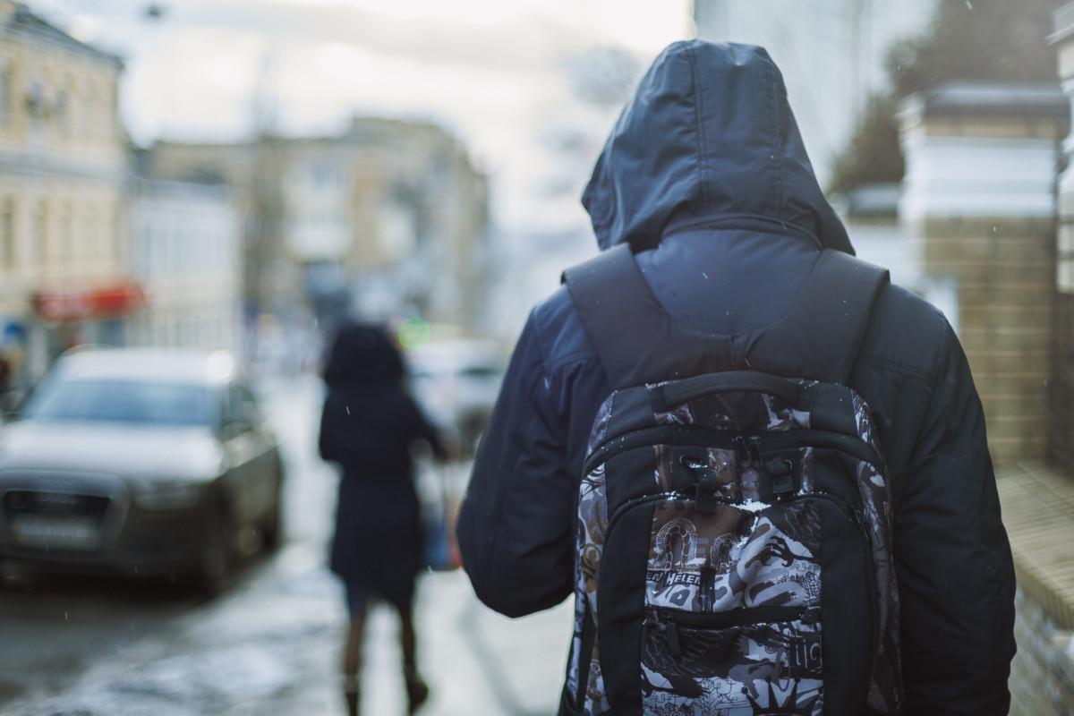 Hipster,Man,In,Hood,Walking,Through,City,Street